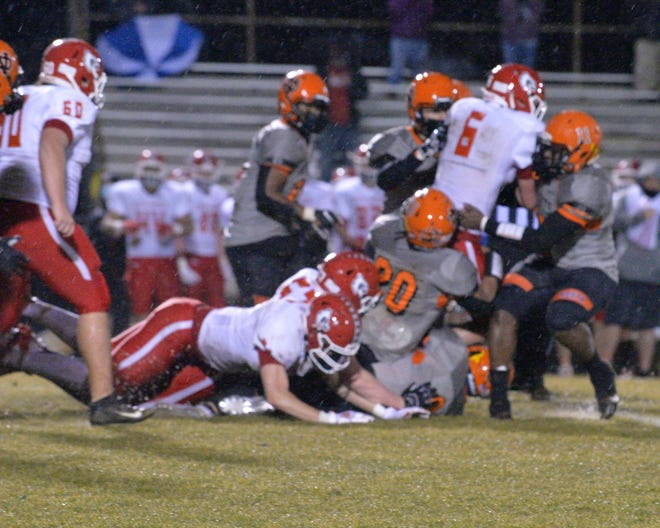 North Davidson's Logan Buis (right) and Darain Green (20) tackle East Surry's Benji Gosnell on Friday at Palmer Field. [Mike Duprez/The Dispatch]