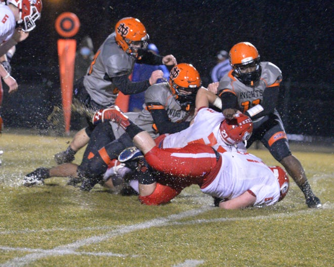 North Davidson's Travarius Moore (right) helps tackle East Surry running back Luke Bullington. [Mike Duprez/The Dispatch]