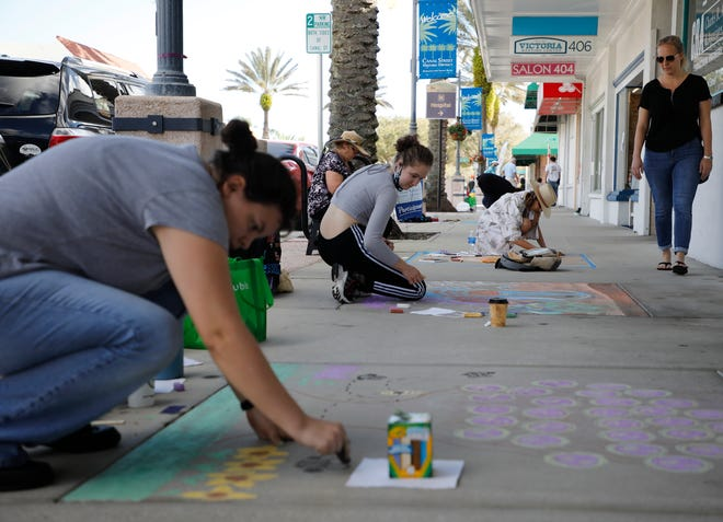 Onlookers walk by and look at the sidewalk paint during the Chalk It Up Event in New Smyrna on Saturday, Feb. 27, 2021.