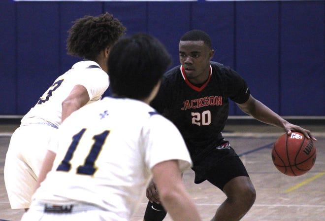 Jackson guard Davin Daniels (20) dribbles against the Winter Park Trinity Prep defense during Friday night's FHSAA Region 1-3A boys basketball final.