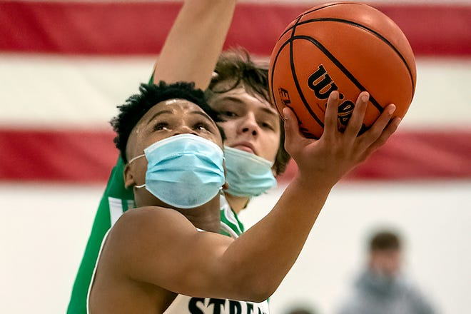 Galesburg junior Jeremiah Babers attempts a reverse layup despite pressure from a Geneseo defender during the Silver Streaks' 74-50 WB6 Conference win over the Maple Leafs on Friday night at the GHS field house.