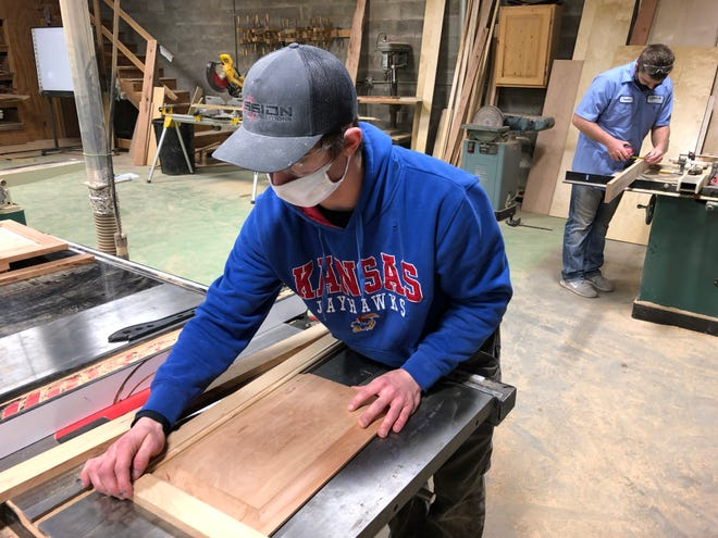 NCK Tech student Dawson Kempt, of Oberlin, joins rails to a panel to build a cabinet door, while student Ben Towner, of Tipton, cuts a dado at the NCK Tech wood shop off 22nd Street.