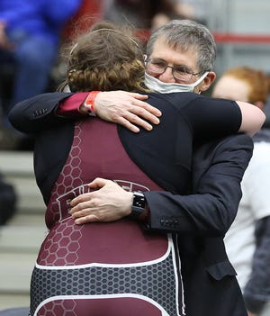 Buhler's Emilie Schweizer gives coach Mike Juby a hug after she wrestled Chapman's Chelsey Armbruster in the 235-pound weight class championship on Friday at the girls Division II state wrestling tournament at the Tony's Pizza Events Center in Salina. Schweizer defeated Armbruster by fall.