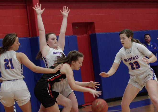 Moberly High School junior Alaina Link raises her arms as she stops the dribble penetration of Hannibal senior Ellie Locke during Saturday afternoon's Class 5 District 15 Tournament opening game. Moving in to assist Link are sophomore Kennedy Messer (#23) and senior Sam Calvert (#21). The Moberly trio helped the fourth-seed Lady Spartans knock off Hannibal 59-39 at home to advance to Monday's 6 p.m. semifinal where they battle top-seed Mexico at the Bulldogs home court.