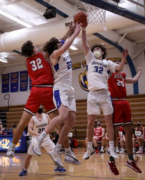 Jefferson's Logan Tackett (22) and Jackson Barath (32) go up for the defensive rebound against New Boston Huron's Ethan Woolery (left) and Cody Egler on Friday, Feb. 26, 2021.