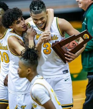 Forest's Jonah Godette congratulates Elijah Russell after Russell made a buzzer-beating three-point shot to win the game. The Forest Wildcats defeated Tallahassee Lincoln, 50-47, in the Class 6A regional finals Friday night.