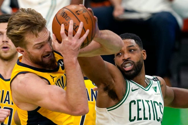 Pacers forward Domantas Sabonis, left, grabs a rebound in front of Celtics forward Tristan Thompson in second-half action on Friday night.