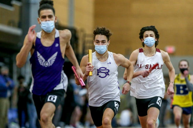 Runners compete in the 4x400 relay on Saturday in the RIIL Boys Indoor State Track Championships at the Providence Career & Technical Academy.
