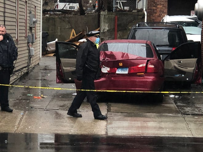 A damaged Honda Accord is blocked by crime-scene tape on a section of Academy Avenue in Providence that was cordoned off by police Saturday afternoon amid investigation of a shooting.