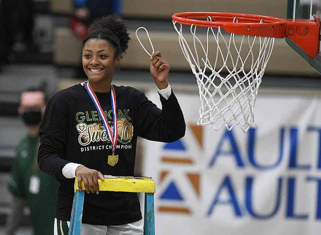 GlenOak senior Aniyah Hall smiles after cutting her piece for the net following the Golden Eagles' Division I district final win over Green on Friday.