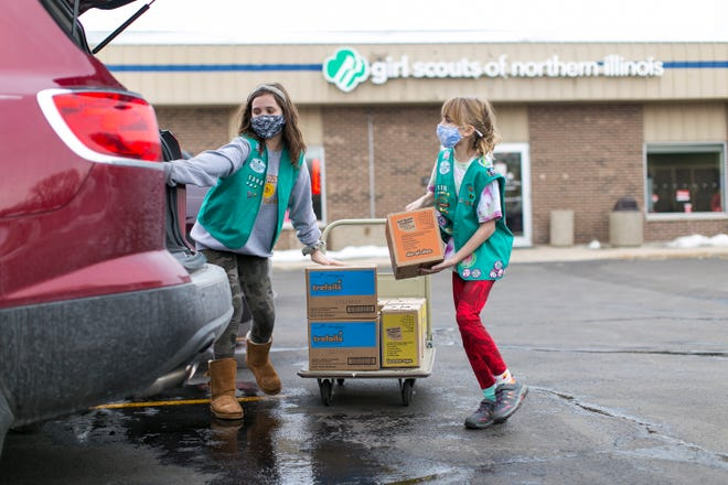 Annabelle Coons, 11, left, and Lucy Berry, 11, of Girl Scouts Troop 1398 load boxes of Girl Scout Cookies  for a customer at Girl Scouts of Northern Illinois on Friday, Feb. 26, 2021, in Rockford.