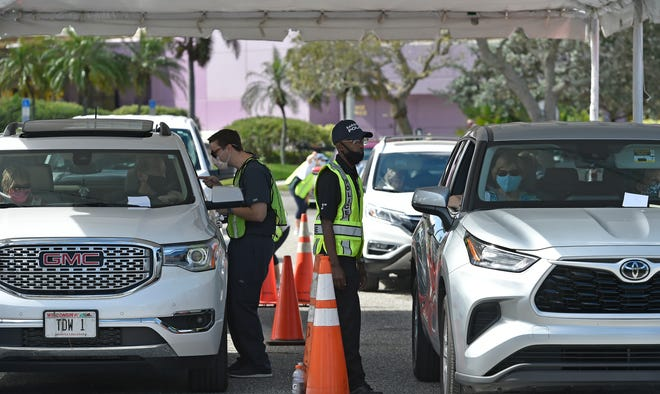 Clinic staffers assist patients during a February drive-thru COVID-19 vaccine clinic in the parking lot of  the Van Wezel Performing Arts Hall. The city of Sarasota will host a second-dose clinic at the same site this weekend.