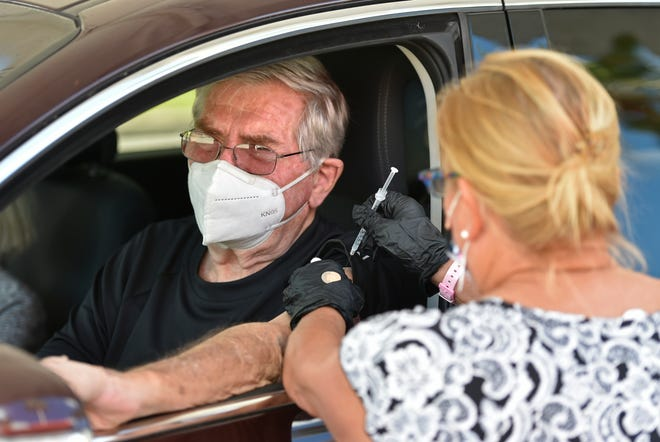Kathleen Cover, a registered nurse who currently is looking for employment, administers the vaccine to Don Zaino, 84, of Venice.