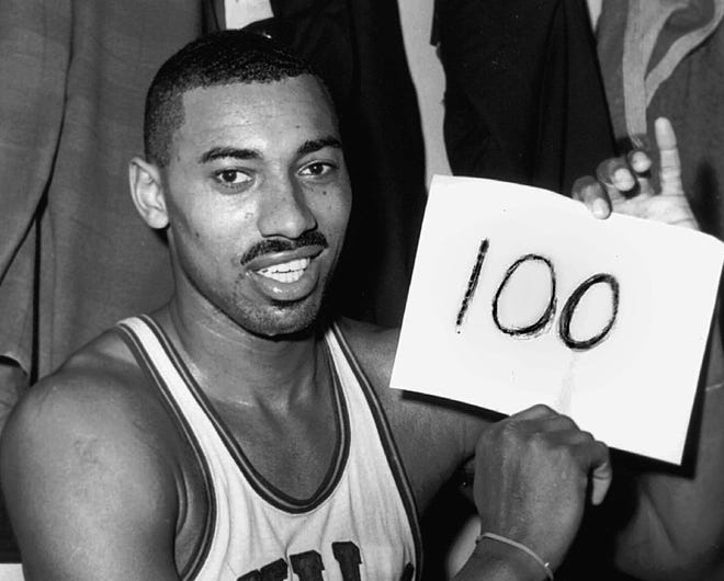 """Wilt Chamberlain of the Philadelphia Warriors holds a sign reading """"100"""" in the dressing room in Hershey, Pennsylvania, after he scored 100 points as the Warriors defeated the New York Knickerbockers 169-147 on March 2, 1962. Paul Vathis/The Associated Press"""