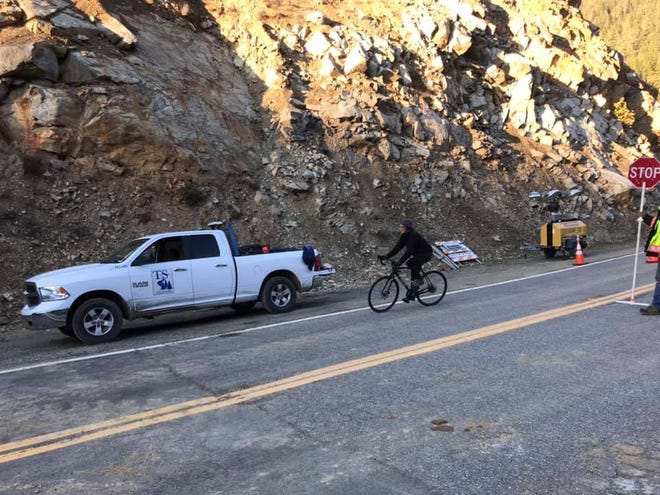 Photos of a bicyclist driving through the narrow one-lane access point on state Route 96 near Happy Camp on Monday (Feb. 23, 2021).  The area is under one-way traffic controls after a mudslide blocked the area in late January, Caltrans said.