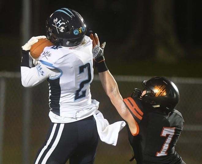 Hoggard's Conrad Newman (left) catches a touchdown during the spring matchup between the Vikings and New Hanover. The longtime rivals' game returns to the season finale for the fall of 2021. [MATT BORN/STARNEWS]