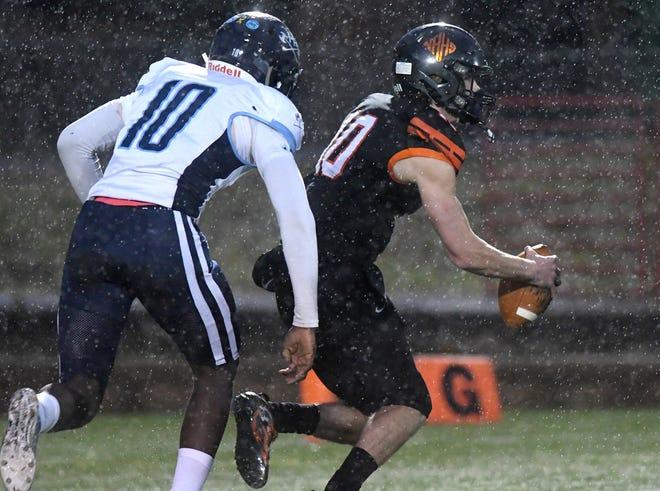 New Hanover quarterback Aliam Appler scrambles through the rain away from the Hoggard defense on Friday night.