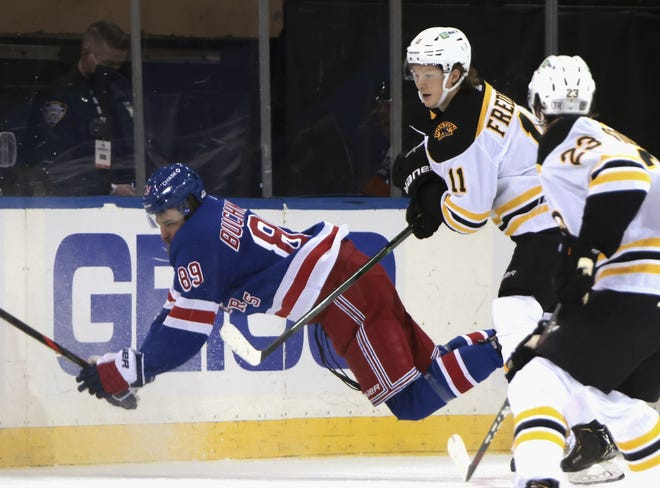 The Bruins' Trent Frederic hits New York Rangers' Pavel Buchnevich during the second period Friday night in New York.