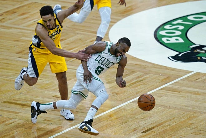 Celtics guard Kemba Walker, right, dribbles the ball as he is grabbed by Indiana Pacers guard Malcolm Brogdon on Friday at TD Garden.