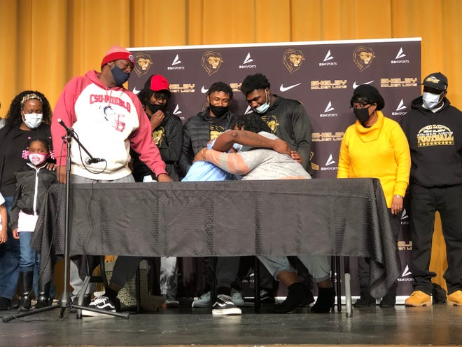 After announcing his commitment to UNC, Shelby junior linebacker Malaki Hamrick (seated on left) celebrated with his mother, Latoya Williams (seated on right), and father, Montral Hamrick (standing on left).