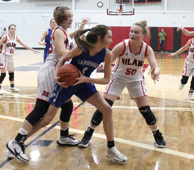 Cambridge sophomore McKinzi Linscott looks for a teammate as Hiland's Kelsey Swihart, left, and Zoe Miller (50) apply defensive pressure during Saturday's Division III District championship game at the Reese Center in Berlin.
