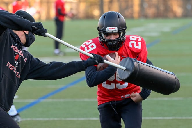Football practices were different this year, and not because they were in February, either. Players had to mask up, before going through the drills like Eli Freingold had to do as he tightly holds onto the ball in this photo, while one of his Marblehead coaches attempts to knock it free.