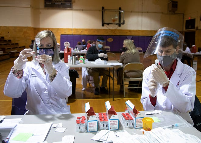 Walgreen pharmacists Heather Creasey, left, and Derrick Erman, right, fill syringes full of the Moderna COVID-19 vaccine at Unioto Local Schools in late February.