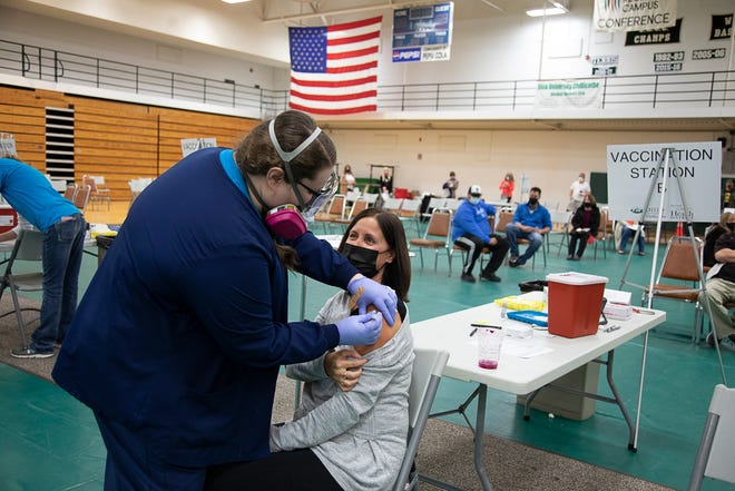 An area teacher receives a vaccine early in the vaccine rollout at the Ross County Health DIstrict's vaccine distribution clinic in OUCs Shoemaker center.