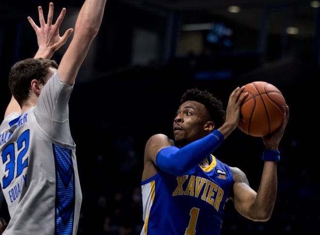 Xavier Musketeers guard Paul Scruggs (1) passes the ball as Creighton Bluejays center Ryan Kalkbrenner (32) guards him in the first half of the men's NCAA basketball game on Saturday, Feb. 27, 2021, at the Cintas Center in Cincinnati.