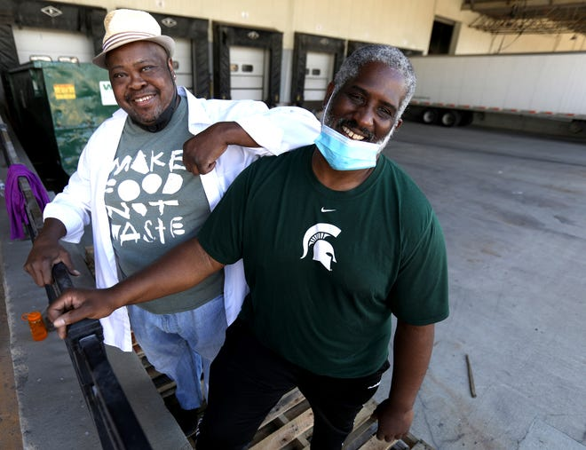 Chef Phil Jones, left, co-founder of Make Food Not Waste, and publicist David Rudolph take a break in the volunteer efforts of moving produce from pallets to vehicles at the loading dock at the TCF Center in downtown Detroit on June 12, 2020. Close to 80,000 pounds of produce and chicken were going to 18 agencies from Detroit to Livonia, Saginaw to Flint and families in need that saw the Detroit Free Press story on Thursday.
