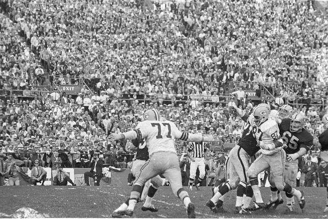 Green Bay Packers defensive tackle Ron Kostelnik (77) reaches out to wrap up Oakland Raiders quarterback Daryle Lamonica during Green Bay's 33-14 victory over Oakland in Super Bowl II at the Orange Bowl in Miami on Jan. 14, 1968.
