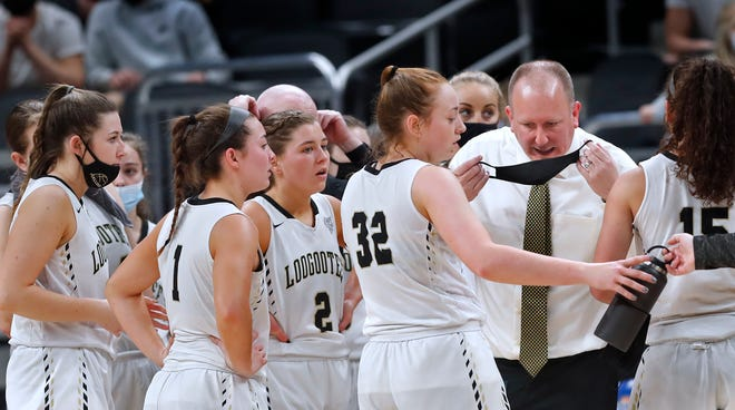 Loogootee High School's head coach Brian Smith puts on his mask to talk to the team during a halftime in the IHSAA girls basketball Class A state final game Saturday, Feb. 27, 2021 at Bankers Life Fiedlhouse.