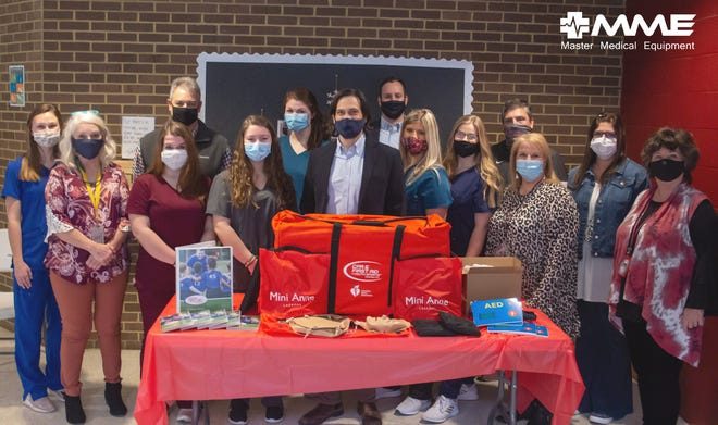 Master Medical Equipment President Mark Taylor (center) and various faculty and staff from Crockett County High School show off the CPR educational equipment before giving it to senior students at the school.