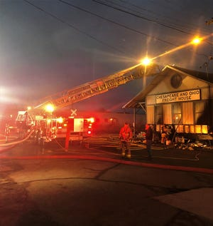 Lancaster firefighters work to patch a roof of the Ohio Fraternal Order of Police Lodge #50 early Saturday morning. The fire was reported around 4:30 a.m. No one was injured in the fire, and it is still under investigation.