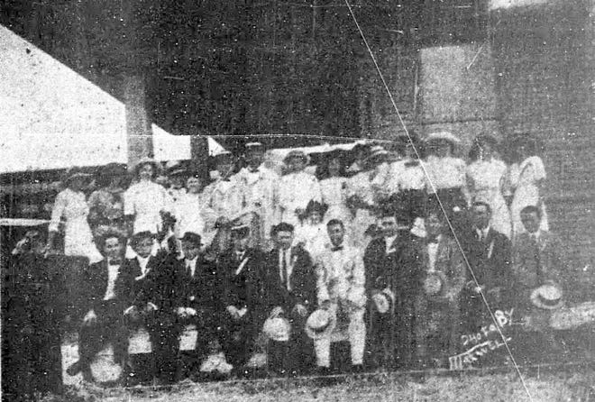 Pictured are St. Landry Clarion employees and guests at their annual picnic in June of 1913. Marshall Thompson is the third person from the right in the front row.  Others in the photo are: (L-R) – Top Row:  Bessie Durio, Judy Breaux, Mrs. E. L. Loeb, Daisy Edwards, Lena Loeb, E. L. Loeb, Y. Andrepont, Mrs. Y. Andrepont, Lillian Jacobs, Mrs. Aaron Jacobs, Mrs. Adolph Jacobs, Juliet Jacobs, Mrs. Geo Vidrine, Felicity Andrepont, Mrs. Alva Smith, Essie Prud'homme.  Bottom Row: Howard Voorhies, Lawrence Andrepont, Geo. Dubuisson, Roy Edwards, R. H. Price, Aaron Jacobs, T. P. Bowden, Marshall Thompson, Geo Vidrine and Alva Smith.