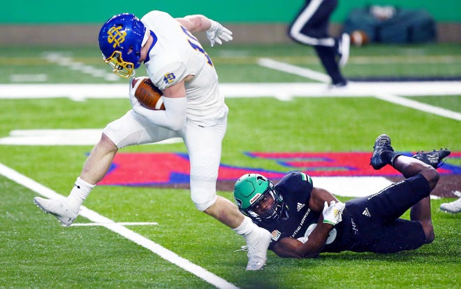 SDSU's Jaxon Janke slips a tackle by UND's Sammy Fort in the first half Saturday in Grand Forks. UND won 28-17. Photo by Eric Hylden/Grand Forks Herald