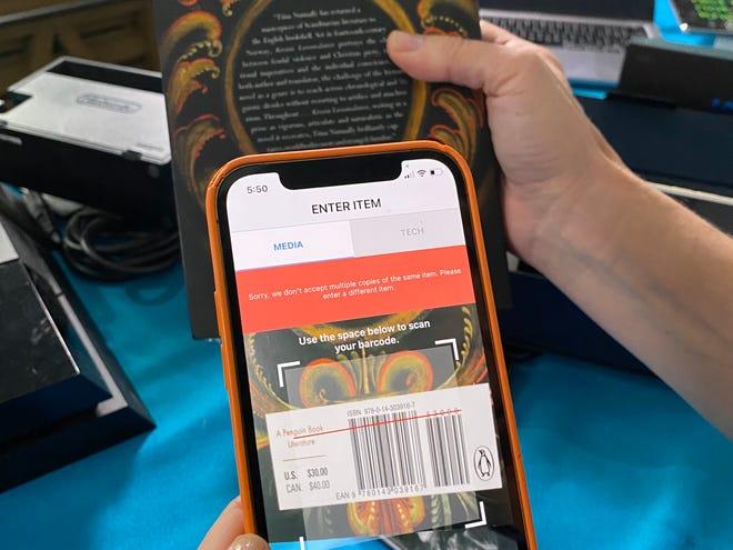 Columnist Jennifer Jolly scans a book using the Decluttr app.