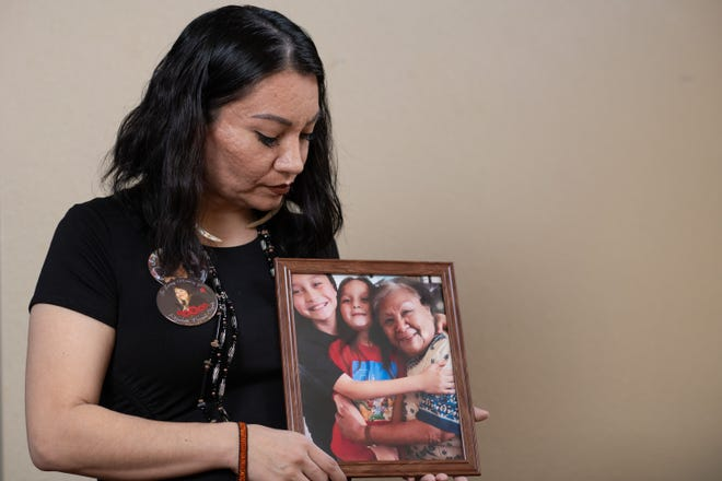 Leticia Aguilar poses for a portrait holding a picture of her gandmother Betty Ann Sigala in her home.