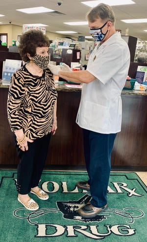 Brian Caswell, owner of Wolkar Drug in Baxter Springs, Kansas, administers a COVID-19 vaccine.