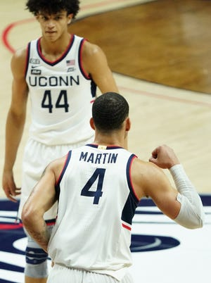 Connecticut Huskies guard Tyrese Martin (4) reacts after making a basket against the Marquette Golden Eagles in the first half at Harry A. Gampel Pavilion.