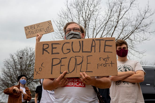 Erik Mackdanz, 46, stands with over 50 people while protesting the Electric Reliability Council of Texas in Austin on Sunday, Feb. 28, 2021.