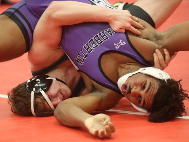 Perry's Logan Shephard controls Barberton's Roosevelt Andrews in the 220 pound weight class at the Division I wrestling sectionals at Wadsworth High school, Saturday. [Mike Cardew/Akron Beacon Journal]