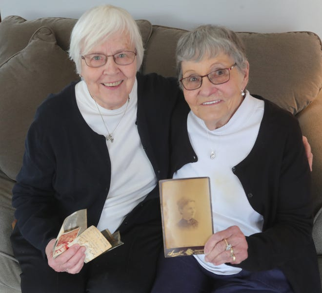 Cuyahoga Falls twin sisters Clara Nicholson, left, and Eleanor Ritchie, both 83, hold photos Sunday that were found in a secret compartment during a remodeling project at their childhood home in Stow. Ritchie is holding a photo of their grandmother Frances Manton Chapman.