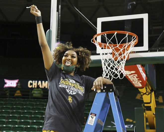 Baylor guard DiDi Richards holds a piece of the net after defeating Kansas State in Waco on Saturday. Baylor celebrated its 11th consecutive Big 12 regular season title and 12th overall.
