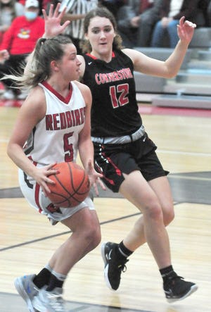 Loudonville's Paige Race (5) takes the ball to the basket past Cornerstone Christian Academy's Aislyn Hurst (12) during the Redbirds' 63-43 win Saturday at Loudonville High School.