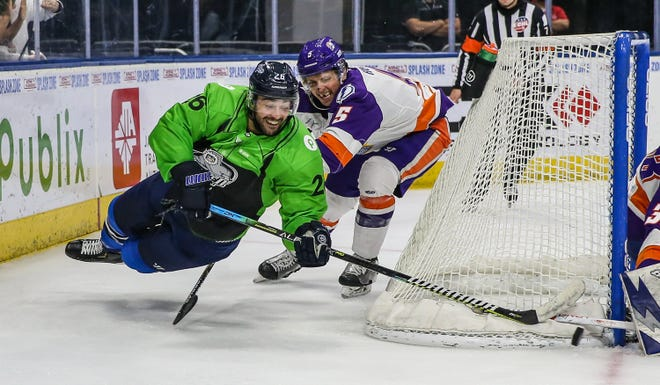 Jacksonville Icemen forward Pascal Aquin (26) looks to center the puck defended by Orlando Solar Bears defenseman Alexander Kuqali (5), right, during the second period on Sunday.