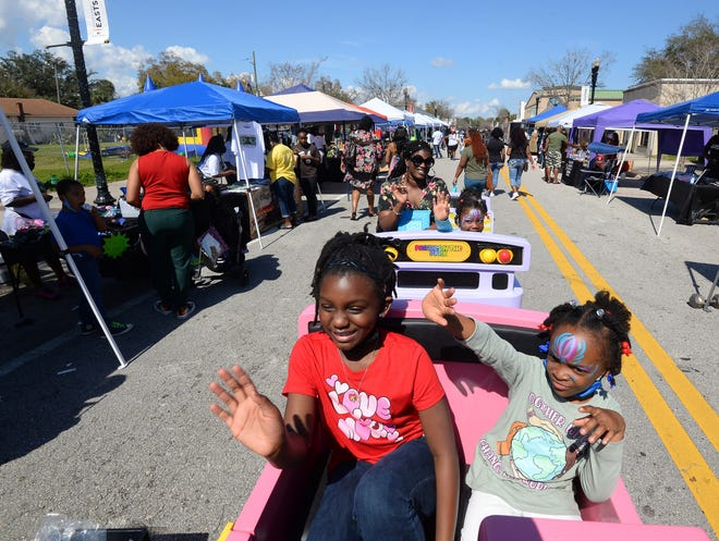 Trinity Stephens, 7, and Egypt Vninig, 6, wave as they ride through Saturday's Melanin Market on a kids train on A. Philip Randolph Boulevard in Jacksonville's historic Eastside. Sunday followed with a Black-nificent Culinary Arts Festival to showcase African American entrepreneurship, chefs and eateries.