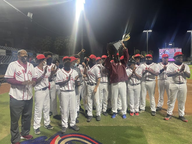 Raines head baseball coach Aaron Austin hoists the A. Philip Randolph Cup after the Vikings defeated Ribault in the High School Heritage Classic.