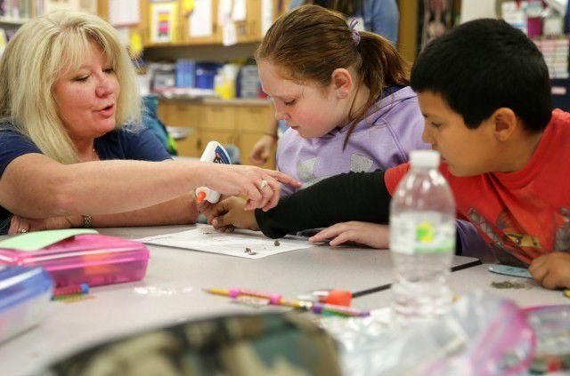 Substitute teacher Crystal Loughran assists students Alyssa Bokus and Isaac Godina during an owl pellet dissection activity at Northwest Elementary School in La Salle. Local leaders are looking for ways to address the teacher shortage affecting the country.