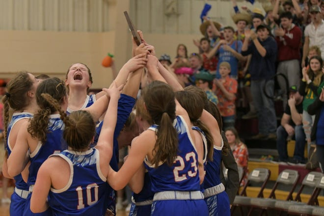 The Scotland County girls basketball team celebrates with its district trophy after beating Schuyler County 42-36 on Saturday.
